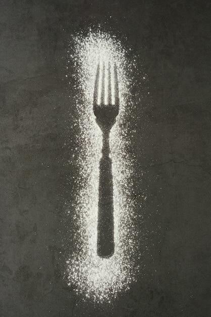 Odcisk widelec sylwetka wykonana z mąki na czarnym tle Premium Zdjęcia