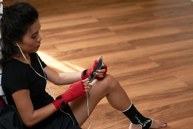 Odgórnego kąta widok wybiera muzyczny ślad na jej smartphone przy przerwą treningową sportsmenka Darmowe Zdjęcia