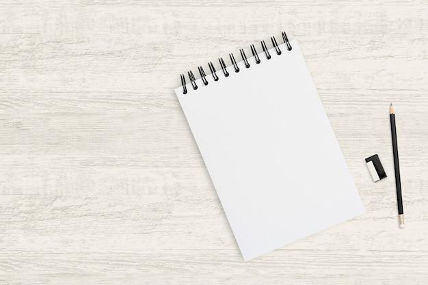 Odgórnego widoku przedmiota tło pusty notatnik i ołówek na drewnianej teksturze. Premium Zdjęcia