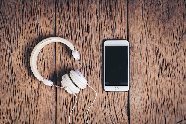 Odgórnego widoku telefonu i hełmofonu drewniany tło Darmowe Zdjęcia