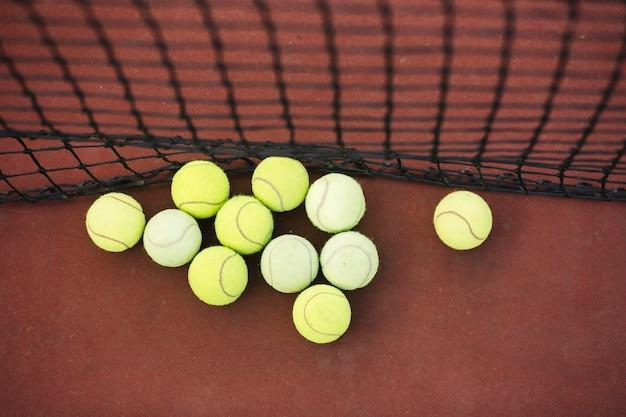 Odgórnego widoku tenisowe piłki obok zarabiają netto na polu Darmowe Zdjęcia