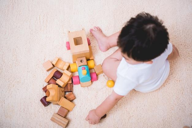 Odgórny Widok Bawić Się Z Zabawkarskimi Blokami Azjatykci Dziecko Premium Zdjęcia