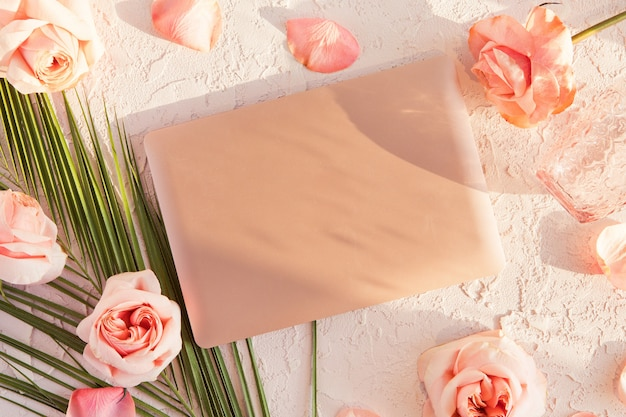 Odgórny widok biurowy żeński biurko z laptopem, tropikalny liść, różowe róże kwitnie na bielu z cieniami i światłem słonecznym Premium Zdjęcia