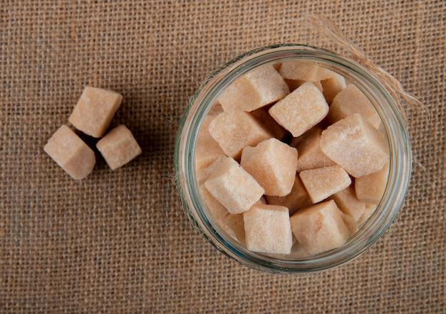 Odgórny Widok Brown Cukieru Sześciany W Szklanym Słoju Na Parcianym Tekstury Tle Darmowe Zdjęcia