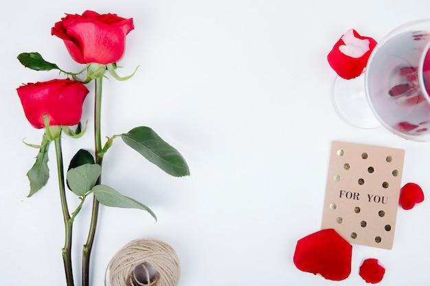 Odgórny Widok Czerwonego Koloru Róże Z Szkłem Czerwone Wino Mała Pocztówka Z Arkaną Na Białym Tle Z Kopii Przestrzenią Darmowe Zdjęcia