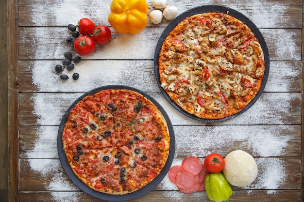 Odgórny widok dwa włoskiej pizzy w drewnianym tle z mąką kropi Darmowe Zdjęcia