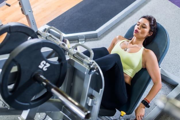 Odgórny Widok Dysponowana Młoda Kobieta Robi Nogi Prasie W Gym Premium Zdjęcia