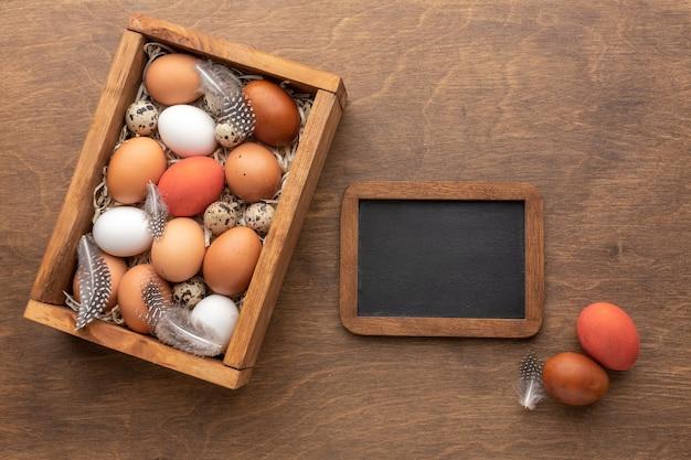 Odgórny Widok Easter Jajka W Pudełku Z Piórkami I Blackboard Darmowe Zdjęcia