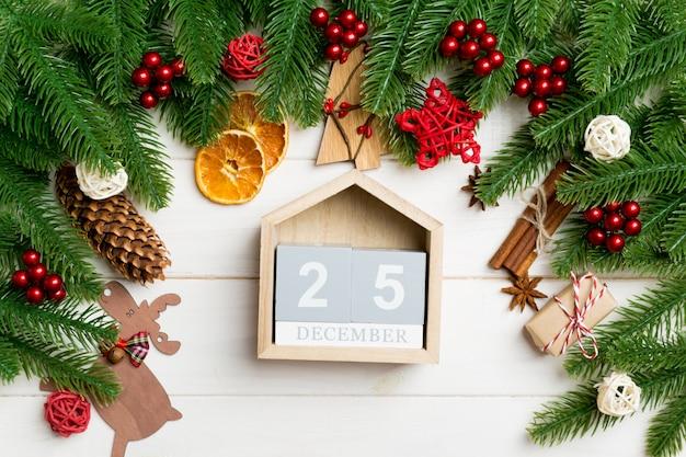 Odgórny Widok Jedlinowe Gałąź Na Drewnianym Stole. Kalendarz Ozdobiony świątecznymi Zabawkami. Dwudziestego Piątego Grudnia. Pojęcie Czasu Bożego Narodzenia Premium Zdjęcia