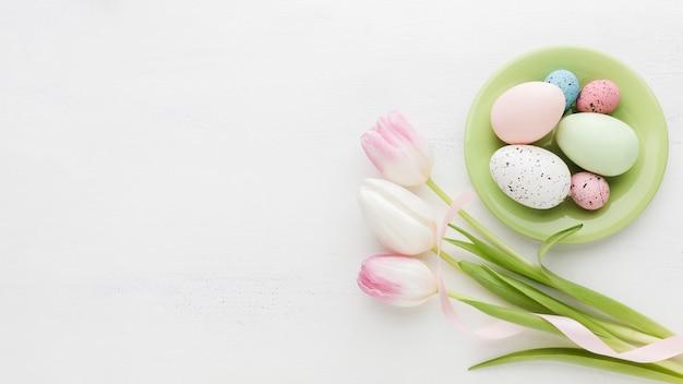Odgórny Widok Kolorowi Easter Jajka Na Talerzu Z Tulipanami Darmowe Zdjęcia