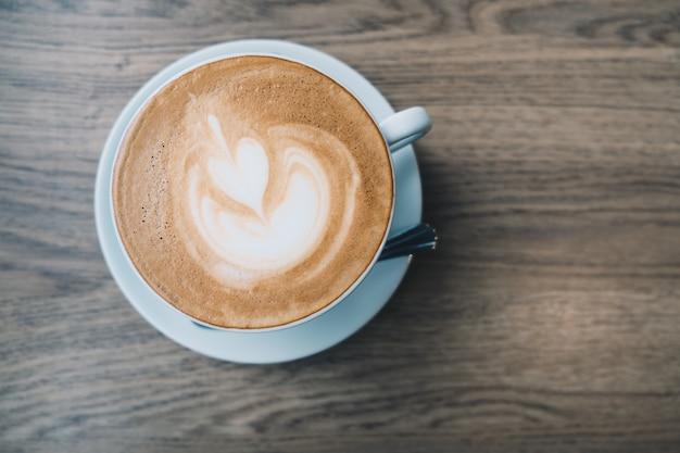 Odgórny Widok Latte Gorąca Kawa W Białej Filiżance Z Latte Sztuką Na Drewnianym Stołowym Tle Premium Zdjęcia