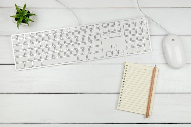 Odgórny Widok Notatnik Z Klawiaturą I Myszą Na Białym Biurowym Biurku Premium Zdjęcia