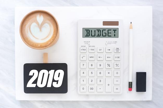 Odgórny Widok Nowego Roku 2019 Budżet Na Kalkulatorze I Filiżanka Na Bielu Marmuru Bloku Premium Zdjęcia