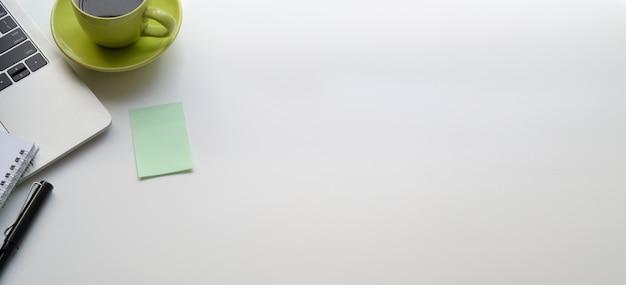 Odgórny widok nowożytny miejsce pracy z laptopem i zieloną filiżanką na bielu stole Premium Zdjęcia