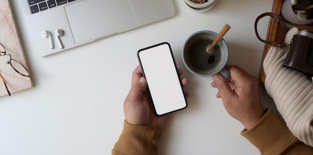 Odgórny widok patrzeje pustego ekranu smartphone mężczyzna podczas gdy trzymający filiżankę Premium Zdjęcia