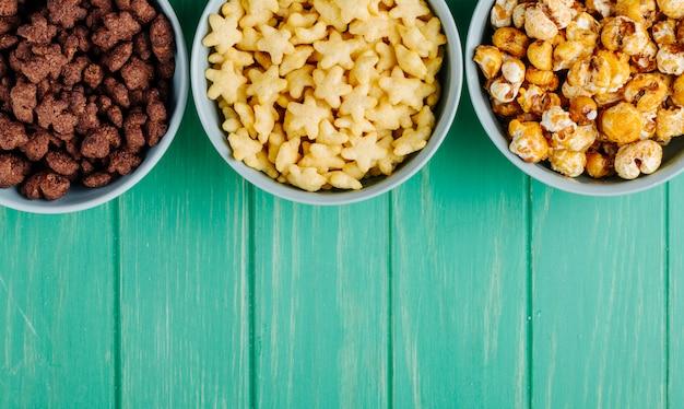 Odgórny Widok Puchary Różnorodni Zboża I Słodki Karmelu Popkorn Na Zielonym Drewnianym Tle Z Kopii Przestrzenią Darmowe Zdjęcia