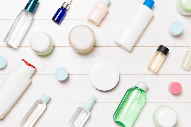 Odgórny Widok Różne Kosmetyk Butelki I Zbiornik Dla Kosmetyków Na Biały Drewnianym Premium Zdjęcia