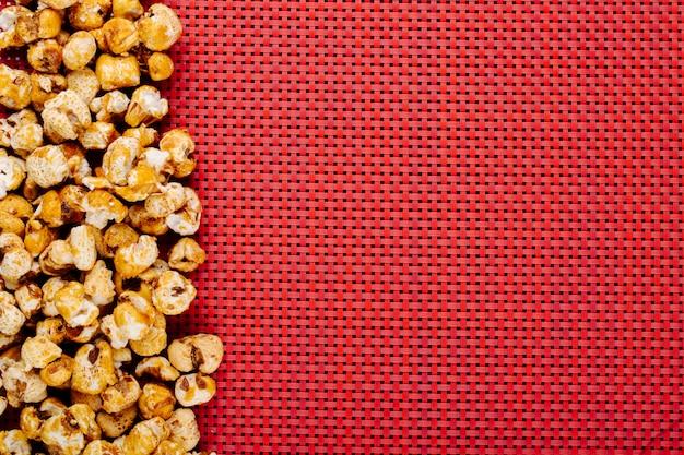 Odgórny Widok Słodka Karmelizująca Wystrzał Kukurudza Przy Lewą Stroną Na Czerwonym Tle Z Kopii Przestrzenią Darmowe Zdjęcia