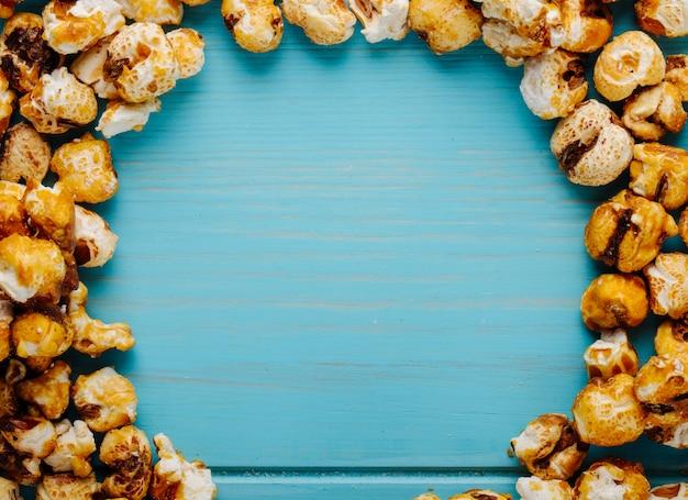 Odgórny Widok Słodki Karmelu Popkorn Na Błękitnym Drewnianym Tle Z Kopii Przestrzenią Darmowe Zdjęcia
