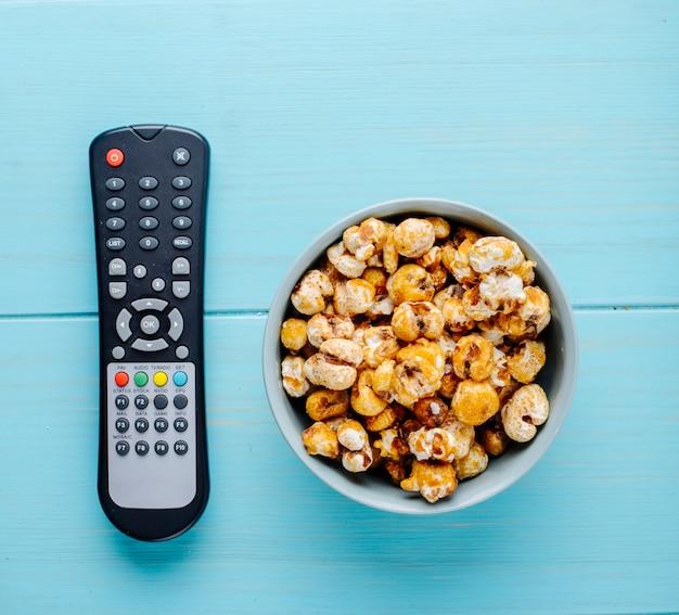 Odgórny Widok Słodki Karmelu Popkorn Z Tv Pilotem Na Błękitnym Tle Darmowe Zdjęcia