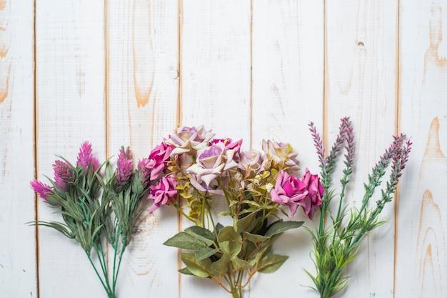 Odgórny widok ślub kwitnie na białym drewnianym tle Premium Zdjęcia