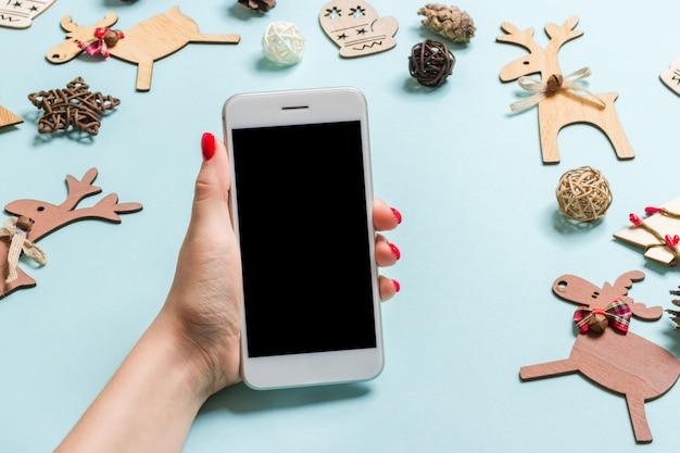 Odgórny widok telefon w żeńskiej ręce na świątecznym błękicie Premium Zdjęcia