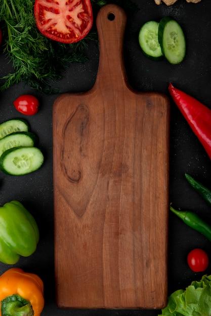 Odgórny Widok Tnąca Deska Z Warzywami Jako Koper Ogórkowy Pomidorowy Pieprz Wokoło Na Czarnym Tle Darmowe Zdjęcia