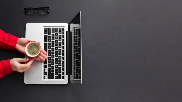 Odgórny Widok Trzyma Filiżankę Kawy Nad Laptopem Na Biurku Ręka Darmowe Zdjęcia