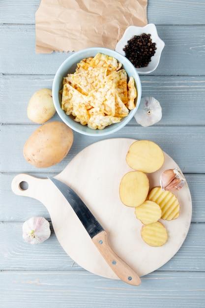 Odgórny Widok Warzywa Jak Pokrojony Kartoflany Czosnek Z Nożem Na Tnącej Desce I Chipsami Z Czarnym Pieprzem Na Drewnianym Tle Darmowe Zdjęcia