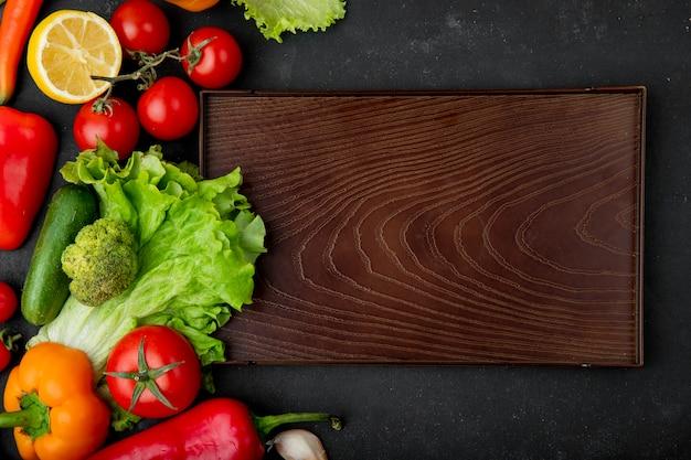 Odgórny Widok Warzywa Jako Brokuł Sałaty Pomidorowy Ogórek Z Cytryną I Tnąca Deska Na Czarnym Tle Darmowe Zdjęcia