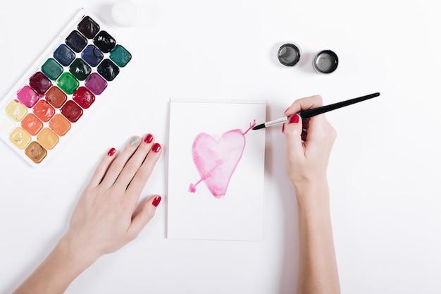 Odgórny Widok żeńskie Ręki Z Czerwonym Manicure'em Malował Akwareli Serce W Notatniku Premium Zdjęcia