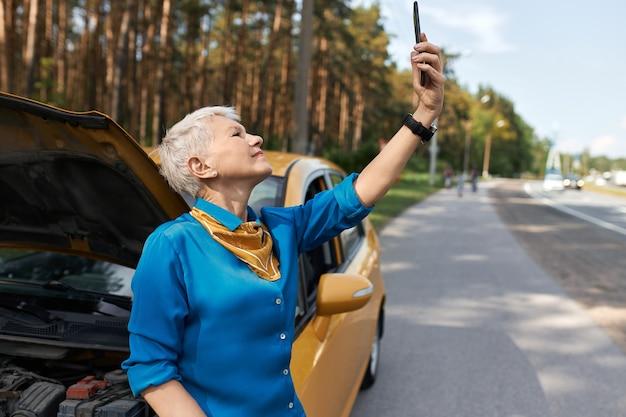 Odkryty Obraz Nieszczęśliwej Kobiety W średnim Wieku Stojącej Na Drodze Przez Uszkodzony Samochód Z Otwartym Kapturem Podnosząc Rękę Z Telefonem Komórkowym, Szukając Sygnału Sieciowego, Próbując Wezwać Pomoc. Darmowe Zdjęcia