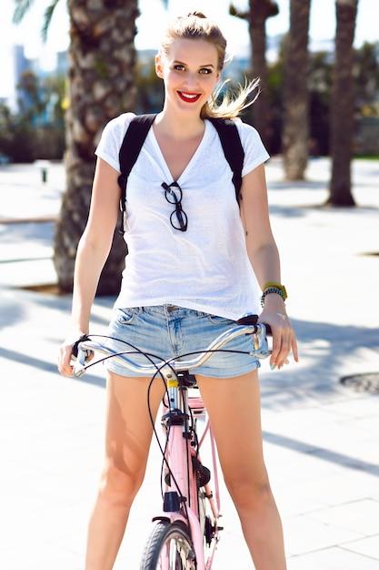 Odkryty Słoneczny Letni Portret Radosnej Szczęśliwej Uśmiechniętej Blondynki, Krzyczącej śmiejąc Się I Bawiąc Się, Jeżdżąc Na Rowerze Retro Vintage Hipster, Ubranie, Jasny Makijaż, Podróże, Wakacje Lato. Darmowe Zdjęcia