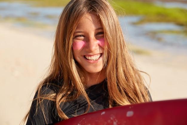 Odkryty Strzał Dobrze Wyglądającej Uśmiechniętej Kobiety Ma Zadowolony Wyraz Twarzy, Nakłada Na Twarz Chorą Warstwę Cynku Darmowe Zdjęcia