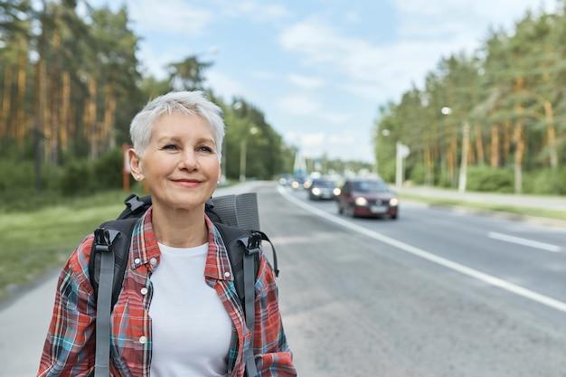 Odkryty Strzał Pięknej Aktywnej Kobiety W średnim Wieku Z Krótką Fryzurą, Niosąc Plecak Idący Wzdłuż Autostrady Podczas Samotnego Autostopu. Darmowe Zdjęcia