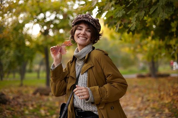 Odkryty Strzał Szczęśliwa Młoda Atrakcyjna Brunetka Kobieta Ubrana W Stylowe Ubrania, Uśmiechając Się Szeroko Podczas Pozowania Nad Niewyraźnym Parkiem Z Liściem W Uniesionej Ręce Darmowe Zdjęcia