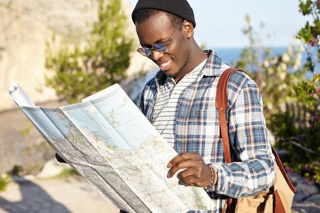 Odkryty Strzał Szczęśliwego Uśmiechniętego Młodego Atrakcyjnego Afrykańskiego Turysty W Malowniczym Krajobrazie, Czytającego Papierową Mapę, Szukającego Trasy I Nowego Zwiedzania, Noszącego Modne Okrągłe Lustrzane Soczewki Darmowe Zdjęcia