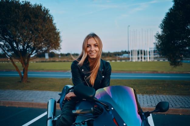 Odkryty Wizerunek Atrakcyjnej Młodej Europejki Z Luźnymi Blond Włosami Siedzącej Na Niebieskim Motocyklu, Ubrana W Kamuflażowe Dżinsy I Czarną Skórzaną Kurtkę Darmowe Zdjęcia