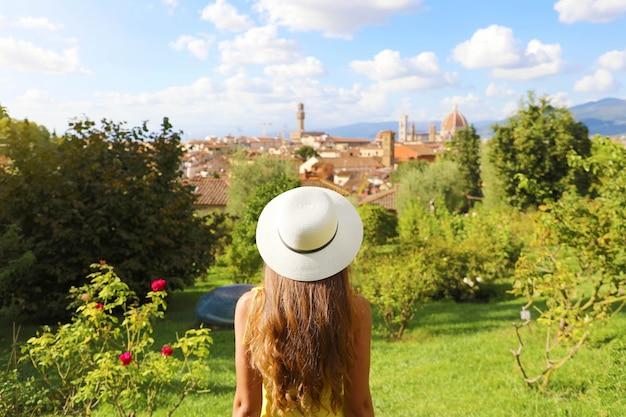 Odkrywanie Florencji. Widok Z Tyłu Dziewczyny Młody Turysta Patrząc Na Panoramę Florencji Między Drzewami W Parku. Turystyka W Toskanii. Premium Zdjęcia