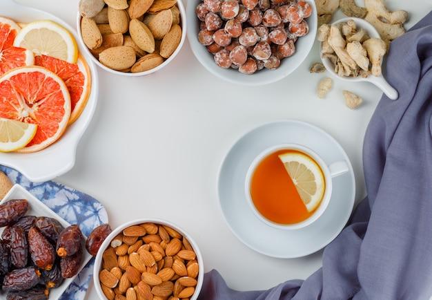 Odmiana Orzechów Z Filiżanką Herbaty, Daktyli, Plasterków Owoców Cytrusowych I Imbiru W Białych Talerzach Darmowe Zdjęcia
