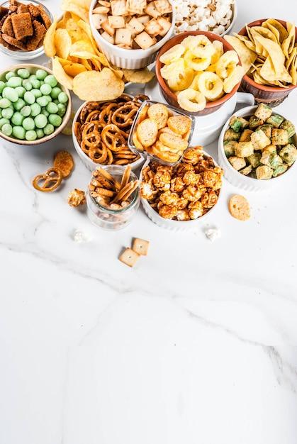 Odmiana Różne Niezdrowe Krakersy Z Przekąskami, Słodki Solony Popcorn, Tortille, Orzechy, Słomki, Bretony Premium Zdjęcia