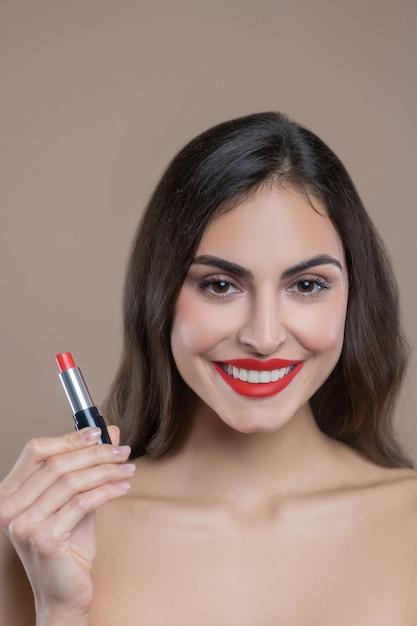 Odpowiedni Ton. Uśmiechnięta Młoda Długowłosa Kobieta Z Odkrytymi Ramionami Z Jaskrawoczerwoną Szminką W Dłoni I Na Ustach Premium Zdjęcia