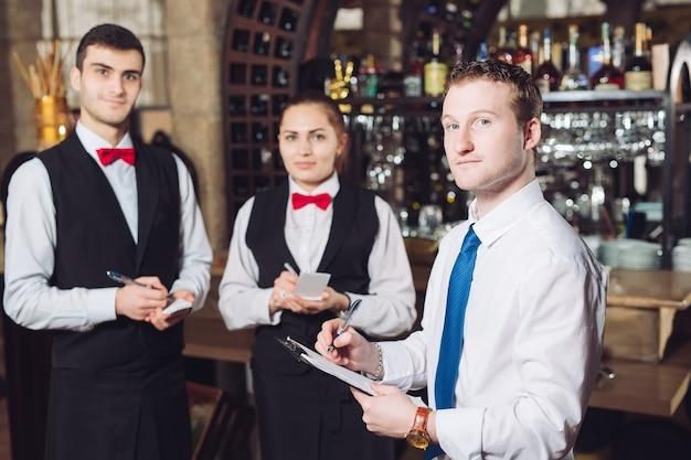 Odprawa menedżera z kelnerami. kierownik restauracji i jego pracownicy. Premium Zdjęcia