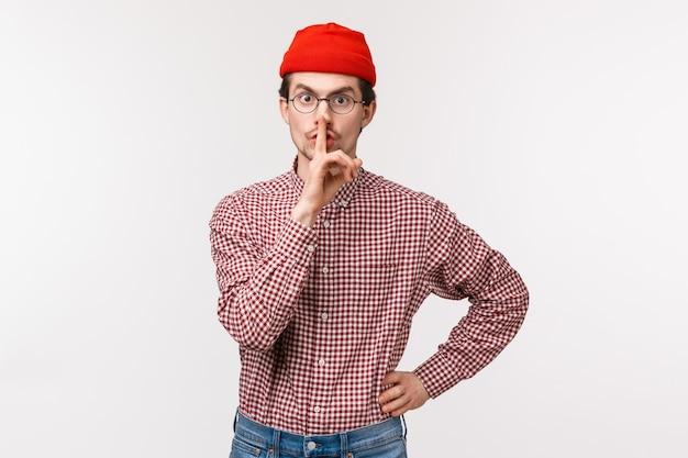 Odważny I Poważnie Wyglądający Młody Mężczyzna W Czerwonej Czapie Drżący Na Nieuprzejmą Osobę Rozmawiającą Głośno Podczas Ważnego Spotkania, Uciszający Palec Wskazujący Na Ustach, Zabraniający Mówienia, Stojący Premium Zdjęcia