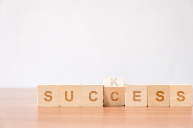 Odwróć zmieniającą się literę na bloku drewna od koncepcji ssania do sukcesu w celu udoskonalenia. Premium Zdjęcia