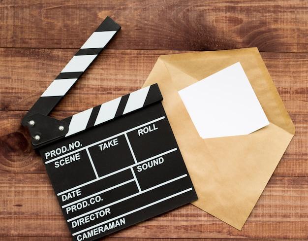 Oglądanie filmu film clapperboard i popcorn na niebieskim drewnianym stole Premium Zdjęcia