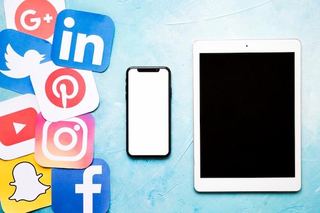 Ogólnospołeczne Medialne Ikony Z Telefonem Komórkowym I Cyfrową Pastylką Na Błękit Malującej ścianie Darmowe Zdjęcia