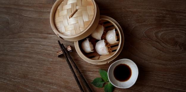 Ogólny Strzał Chińskiej Parze Kluski W Bambusowym Parowcem Z Chopstick Premium Zdjęcia