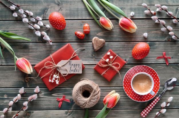 Ogólny widok drewniany stół z wiosennymi dekoracjami, filiżanką kawy, opakowanymi prezentami, kwiatami i pisankami Premium Zdjęcia