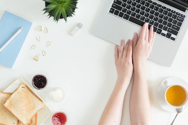 Ogólny widok laptopa, świeże kanapki, filiżankę zielonej herbaty i telefon komórkowy na białym stole pulpitu. kobiety biznesu i śniadania pojęcie, odgórny widok i mieszkanie nieatutowi Premium Zdjęcia